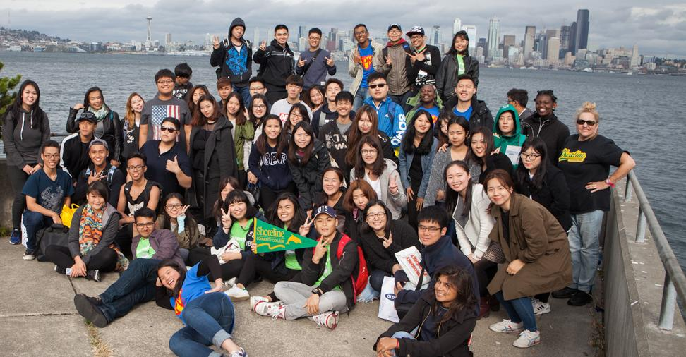 New students pose for a picture at Alki Beach in West Seattle with the Downtown Seattle Skyline across the Puget Sound behind them.