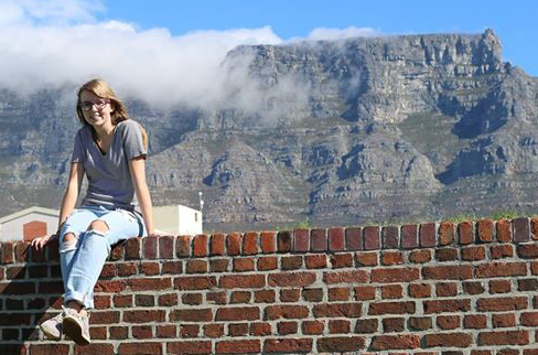 Brenna in Cape Town sitting on a brick wall with the iconic Table Mountain behind her.