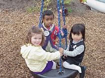 Children playing on tire swing at childcare center playground